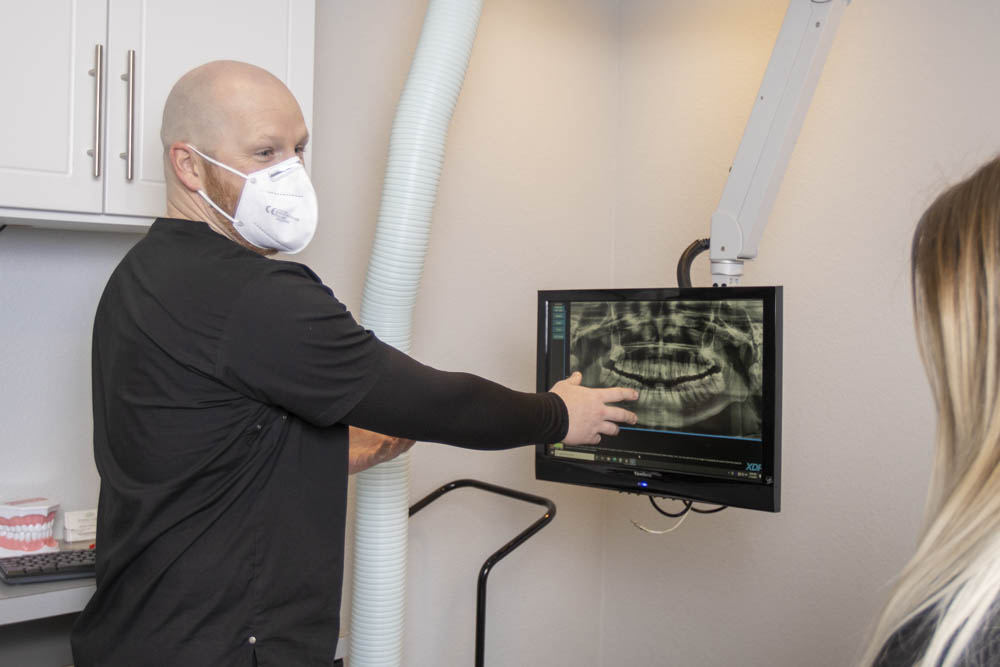 A dental hygienist points to a dental x-ray while speaking to a patient