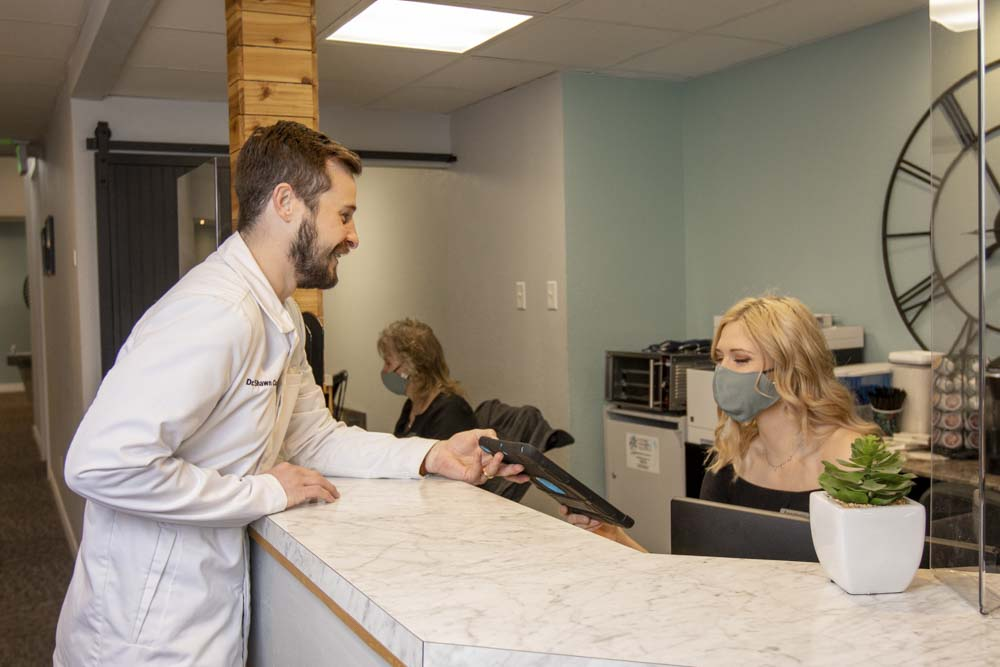 A receptionist speaking to Dr. Custer at the front desk of Park View Family Dental
