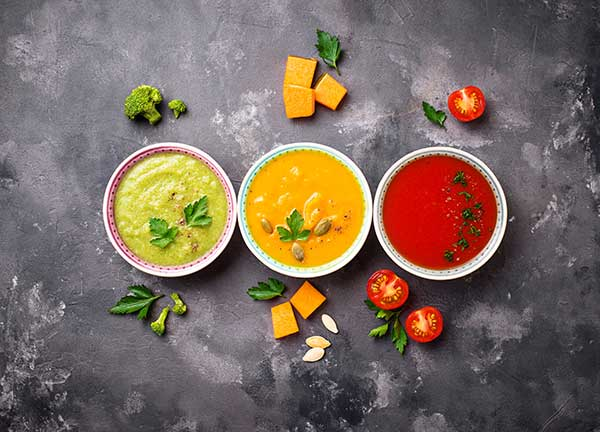 three different soups, one green, one orange and one red soup in bowls next to each other